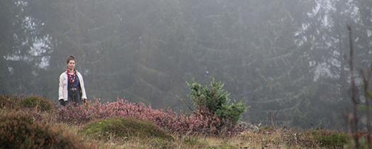 Pfadfinderin im Nebel auf einem Hügel.